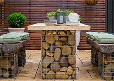 Use gabion baskets – or make your own using steel mesh – fill with pebbles or stone and add reclaimed wood or railway sleeper tops and you have a modern ...