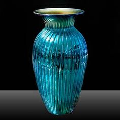 Lundberg Studios   In every way, this is a glassmaker's classic. The superb form, the ribs, the glowing blue and gold iridescent finishes, and Lundberg Studios' very talented artists all work together to produce this true classic. For a change, I photographed this in the gallery so you get a better sense of the contrast between the matte iridescent gold lining, and the glossy blue reflective exterior.