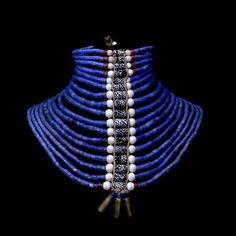 Dinka necklace. Beaded neck ornament, Sudan.This particular neck ornament, with its central band of patterned Venetian beads and brass cartridge cases, would be worn by a Dinka man at or shortly before his wedding to show his eligibility and the wealth of his family in cattle. The beads themselves would either have been traded across the savannah from West Africa or brought inland from the East African coast.