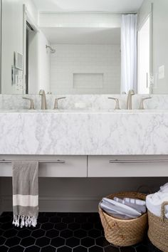 A large mirror reflects the white subway tile shower walls in this bright, contemporary bathroom. A gray and white marble floating vanity surrounds double sinks with stainless steel faucets. Built in drawers and wicker baskets provide storage space over the black hexagon floor tiles.