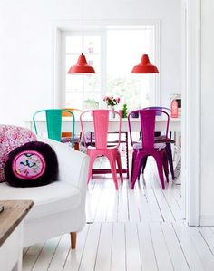 White dining room table, colorful chairs, and colorful hanging lights.