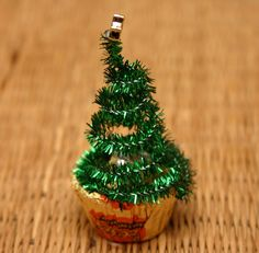 Easy Christmas craft to put together with kids. All you need is Mini Reese's Peanut Butter Cups, a green tinsel pipe cleaner, a star bead and a dab of glue to attach the tree to it's base.