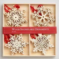 Lend wintry texture to your tree with a flurry of wooden snowflakes, expertly laser-cut for delicate detail. Packed in a wooden gift box, the set includes 12 ornaments in four designs, each fitted with a red ribbon for hanging.