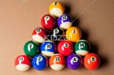 top view of balls arranged on pool table. - Overhead shot of shiny colorful pool balls arranged in triangle on pool table.