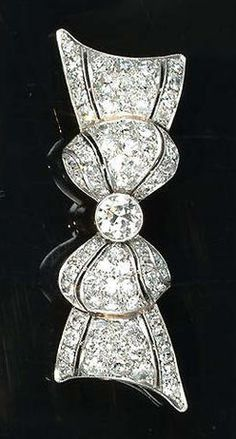 A diamond bow brooch, circa 1920, the tied ribbon bow with pierced detailing, millegrain-set with old brilliant-cut diamonds, to a pierced scroll gallery, Austrian assay marks, makers mark G.B, length 5.0cm., diamonds approximately 3.90 carats total