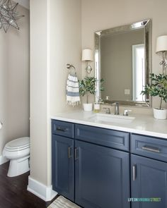 Guest bathroom with navy blue thermafoil cabinet, silver faucet, mini olive trees, and sconces. Blue Decor, Blue Cabinets, Upstairs Bathrooms, White Ceramic Lamps, Silver Bathroom, Silver Faucet, Spring Home, House Tours, Guest Bathrooms