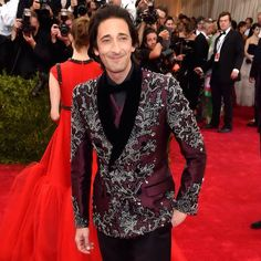 """Adrien Brody wearing a Dolce&Gabbana Alta Sartoria double-breasted embroidered tuxedo jacket in burgundy Mikado with shawl lapel in black velvet; vest in burgundy Mikado; classic trousers in superfine black gabardine; black tuxedo shirt; black bow tie; and lace-up shoes in black velvet to celebrate """"China: Through The Looking Glass"""" Costume Institute Benefit Gala at Metropolitan Museum of Art on May 4, 2015 in New York City. #metgala #metball #dolcegabbana #adrienbrody"""