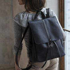 Backpack made from blue durable leather. Its perfect option for travel, study or for work. Backpack closes by straps and buckle. Backpack consist of large main compartment, inner pocket and external pocket. You can worn bag in your hand or on shoulder strap. Shoulder straps of backpack
