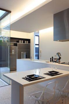 Une belle cuisine design avec chaises de bar transparentes