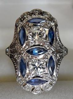 Art Deco diamond and sapphire ring for sale at ArtifactJewels on Etsy. This ring is made from 18k gold with a solid platinum top and is inlaid with  two round brilliant cut diamonds (1.10 cts), seven sapphires (1 carat), and 16 small mine cut diamonds (.40 carats). Via Diamonds in the Library.