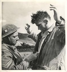 """1943- A soldier of the British 1st Army, searches a German paratrooper for weapons, after he and other Axis troops were captured following a skirmish near Sejanane in the """"Tally Ho"""" corner of Northern Tunisia."""