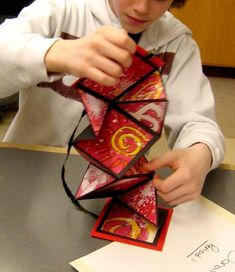 "These small, square books ""explode"" into a series of square and triangular pages when you open them. Each student constructed their own book with decorative papers, cardboard, ribbon, and construct…"