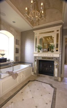 Large Bathroom with Alcove Bathtub containing: Lavish Shelf Top Fireplace with Classic Style Chandelier also Gray Wall Tile plus Chrome Finished Tub Faucet together with Outlined Floor Tile