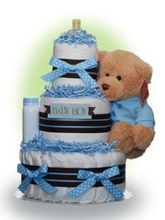 "Our Lil' Darling Boy diaper cake features an adorable plush teddy bear from Gund.  Also included are an ample set of diapers and a starter kit of baby care items from Johnson and Johnson.  The new mom will think of you as she uses these baby care necessities during the daily care of her ""Lil' Darling"". Only $67.00"