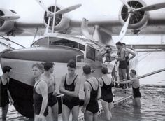 """""""Bathing Beauties"""" US Navy Personnel assist with the arrival of the 1st PanAm S 42 proving flight to Honolulu. 1935."""