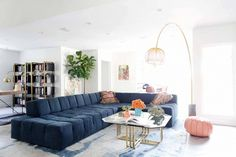 Blue couch, glass top coffee table, tall lamp, colorful cushions, black shelves, plants, artwork