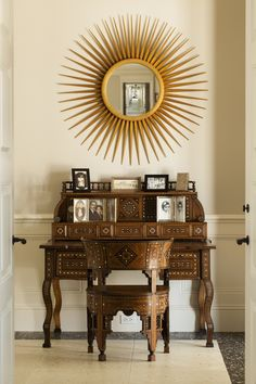 Good design from different eras unites; an heirloom desk from Donna Shalala's family sits under a large-scale sunburst mirror by Albert Hadley.