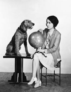 Actress Dorothy Sebastian checks out the world globe with Banjo, an Airedale Terrier who has crossed the Atlantic nine times. Hollywood, CA c. 1929