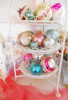 Displaying old ornaments in a tiered dish. They are so beautiful to look at you don't even need the tree. I stash them in bowls and  large apothecary jars.