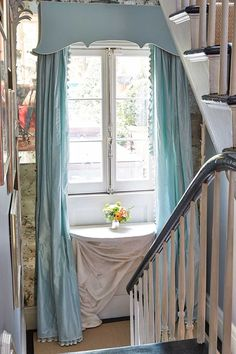 Stair landing in Miles Redd's New York townhouse with silk draperies and a wall-mounted console table