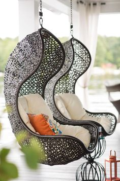 A pair of curved and cushioned wicker swings offer a place to sit back and relax on the elevated, lakeside deck.