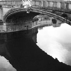 The reflection of Ponte Trinita in the Arno river in Florence, Italy. The bridge was supposedly designed by Michelangelo.