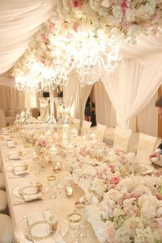 These white filmy curtains, chairs, flowers and decor plus the pretty chandeliers is over-the-top in femininity - but is it too girly for guys at a wedding?