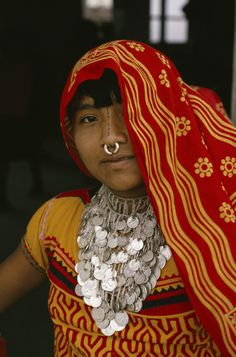 A Cuna Indian woman dons elaborate jewelry and face paint.