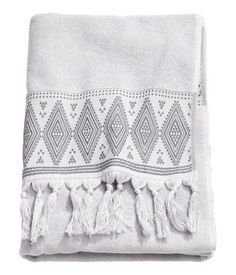 Light gray. Bath towel in soft cotton terry with an embroidered pattern and tassels on short sides.
