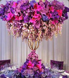Arranjo floral alto, cores fortes em roxo e rosa.