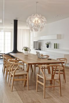 """The interior scheme prevents clutter in a variety of creative ways, including concealing a heat pump in the walls and installing flush-fitting LED spotlights. The architects explain, """"Since the redesign, the prevailing impression is one of spaciousness, the suffusion of light and simple elegance.""""  A statement-making Hope Suspension Light by Luceplan is an elegant addition to the living area. The table, which was designed by the architects and fabricated by VHB Memmingen, is surrounded by…"""