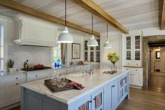 Farmhouse kitchen features wood beams on ceiling accented with modern white pendants over gray center island topped with white marble countertop as well as sink paired with gooseneck faucet.