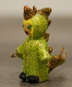 DIY Halloween decoration. Peg doll wearing a stegosaurus costume made with paper mache and glitter.