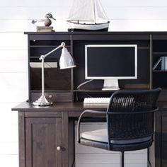 este escritorio de madera està en el estudio. sobre està un ordenador y una làmpara blanca