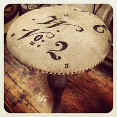 Antique cast iron foot stool with antique German grain sack upholstery