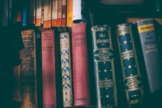 Classic old books with hardback arranged on a bookshelf in a library.