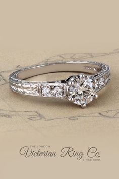 This hand engraved diamond engagement ring is made in the Art Deco style. The central diamond is a round brilliant-cut and is GIA graded. The platinum band has a flat profile. #rounddiamondengagementrings #artdecoengagementring #vintagestyle #handengravedrings #flatprofileengagementring Engagement Rings Uk, Round Diamond Engagement Rings, Diamond Wedding Rings, Wedding Ring Bands, Matching Wedding Rings, Gold Solitaire Ring, Laurel Leaves, Engraved Rings, Hand Engraving
