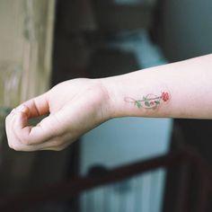 Tatuaje de una rosa dibujando una clave de sol situado en la...