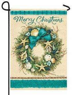 Seaside Christmas themed garden flag. Starfish, seashells and aquatic greenery is all arranged into a beautiful Christmas wreath against a sand colored background. The wreath is finished with a bright