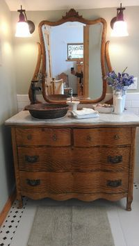 Beautiful antique dresser I turned into a bathroom vanity with a marble top and copper sink.