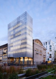 M3A2 Cultural and Community Tower by Antonini+Darmon Architectes  The reflective yet translucent façade of perforated corrugated metal skin allows the solid volume to seem lightweight and ephemeral.