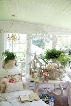 A layering of antique containers and vintage accents lends a cozy, shabby-chic appearance to this sun porch.