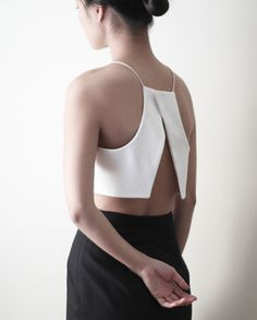 White crop top with open back and black trousers