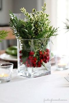Natural Glass Jars Tutorial: Use natural and fresh elements to liven up your table. To create this beautiful decoration, fill a glass jar with water, cranberries, and greens.