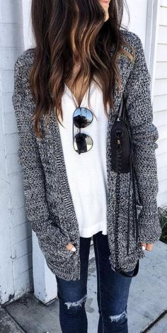 Para el invierno La chaqueta grisa, el suéter blanco, las gafas de sol negras, la bolsa negra, los jeans azules Cuestan $184/171.12€