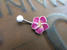 Lovely pink plumeria on a 14 gauge, surgical steel barbell. The bar is 8mm long. The flower is about 13mm at the widest point. Each flower will be