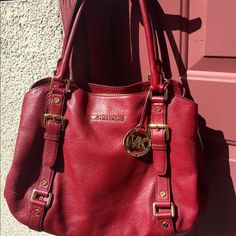 MAKE OFFERMichael Kors Bedford LG Satchel Maroon Gorgeous Michael Kors Bedford. Genuine leather, maroon with gold details. Three large pockets (one zipper pocket,two buttoned). Side of bag has extension buttons to make the bag larger. Lots of details. One of my favorite bags, barely used! Michael Kors Bags Shoulder Bags