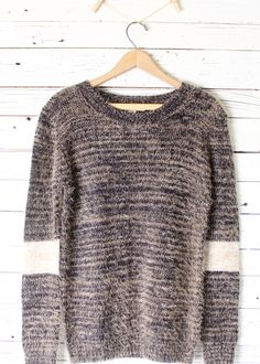 Soft acrylic nylon blend pull over that pairs great with jeans and leggings this fall. Super weave of colors of tan, dark blue and cream with an accent band around each sleeve.     Imported  Acrylic/Nylon  22 inch bust and 29 inches long (taken from size small, add 1/2 inch for next size ...