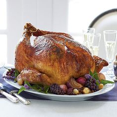 Roasted Turkey with Béarnaise Butter | This classic roasted turkey is made even more divine with a rich Béarnaise Butter. Garnish with roasted onions, fresh herb sprigs, and grapes.
