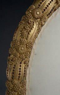 ARMAND ALBERT RATEAU (1882-1938) Tête de lit de forme hémisphérique en bois richement et finement sculpté dune guirlande à décor floral et végétal doré patiné. Support en bois laqué. Travail circa 1920. H: 107 cm, L: 142 cm